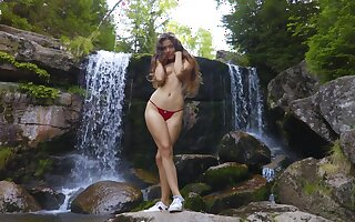 Wide hipped Latina teen with a big exasperation posing half naked by the waterfall