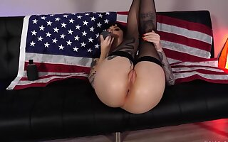 Colleen thrusts sex toy into fanny on the top of the black leather sofa